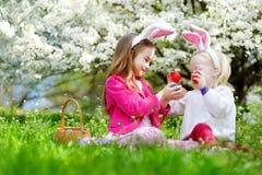2 прелестных маленьких сестры охотясь для пасхального яйца в зацветая весне садовничают Стоковое Изображение RF