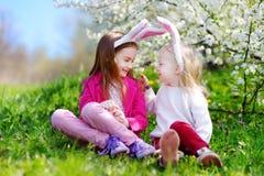 2 прелестных маленьких сестры охотясь для пасхального яйца в зацветая весне садовничают Стоковые Фото