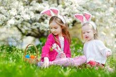 2 прелестных маленьких сестры охотясь для пасхального яйца в зацветая весне садовничают Стоковые Изображения