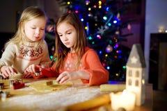 2 прелестных маленьких сестры печь печенья рождества камином Стоковое Изображение