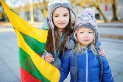 2 прелестных маленьких сестры празднуя литовский День независимости держа tricolor Lithuanian сигнализируют Стоковое Фото