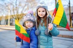 2 прелестных маленьких сестры празднуя литовский День независимости держа tricolor Lithuanian сигнализируют Стоковая Фотография