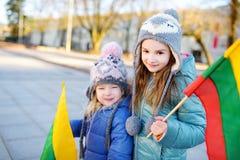 2 прелестных маленьких сестры празднуя литовский День независимости держа tricolor Lithuanian сигнализируют Стоковые Фотографии RF