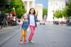 2 прелестных маленьких сестры празднуя литовский день государственности держа tricolor Lithuanian сигнализируют в Вильнюсе Стоковое Изображение