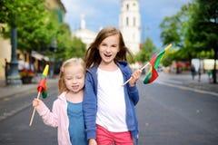 2 прелестных маленьких сестры празднуя литовский день государственности держа tricolor Lithuanian сигнализируют в Вильнюсе Стоковое фото RF
