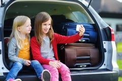 2 прелестных маленьких сестры принимая фото себя перед идти на каникулы с их родителями Стоковые Фотографии RF