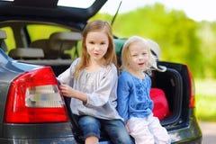 2 прелестных маленьких сестры сидя в автомобиле Стоковые Изображения RF