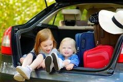 2 прелестных маленьких сестры сидя в автомобиле Стоковые Фото