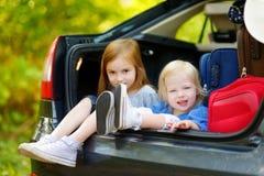 2 прелестных маленьких сестры сидя в автомобиле Стоковое Изображение RF