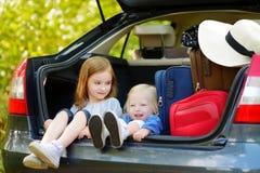 2 прелестных маленьких сестры сидя в автомобиле Стоковые Изображения