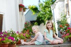 2 прелестных маленьких сестры сидя среди баков цветков на теплый и солнечный летний день Стоковое Фото