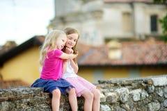 2 прелестных маленьких сестры смеясь над и обнимая на теплый и солнечный летний день Стоковые Изображения RF