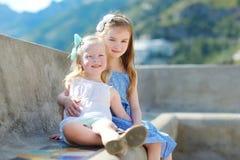 2 прелестных маленьких сестры смеясь над и обнимая одином другого на теплый и солнечный летний день Стоковое фото RF