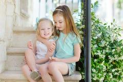 2 прелестных маленьких сестры смеясь над и обнимая одином другого Стоковое Изображение