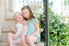 2 прелестных маленьких сестры смеясь над и обнимая одином другого Стоковые Фото