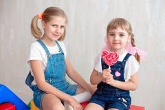 2 прелестных маленьких сестры смеясь над и обнимая одином другого принимая леденец на палочке Стоковые Фото