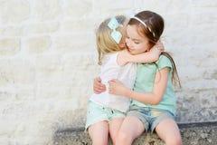 2 прелестных маленьких сестры смеясь над и обнимая Стоковое Фото