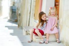 2 прелестных маленьких сестры смеясь над и обнимая Стоковое Изображение RF