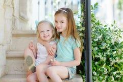 2 прелестных маленьких сестры смеясь над и обнимая Стоковая Фотография