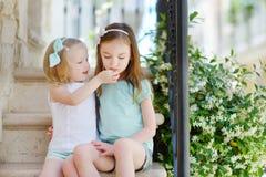 2 прелестных маленьких сестры смеясь над и обнимая Стоковое фото RF