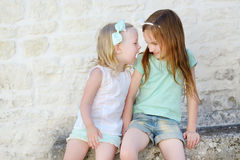 2 прелестных маленьких сестры смеясь над и обнимая Стоковые Изображения