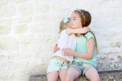 2 прелестных маленьких сестры смеясь над и обнимая Стоковые Фото