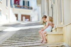 2 прелестных маленьких сестры смеясь над и обнимая Стоковые Фотографии RF
