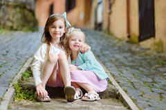 2 прелестных маленьких сестры смеясь над и обнимая Стоковые Изображения RF