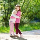 2 прелестных маленьких сестры смеясь над и обнимая Стоковая Фотография RF