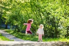 2 прелестных маленьких сестры смеясь над и скача Стоковое Изображение RF