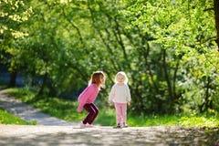 2 прелестных маленьких сестры смеясь над и скача Стоковые Изображения RF