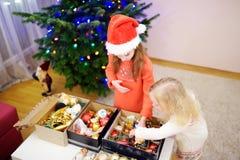 2 прелестных маленьких сестры украшая рождественскую елку Стоковое фото RF