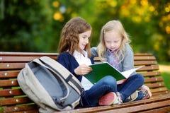 2 прелестных маленьких школьницы изучая в городе паркуют Стоковое Фото