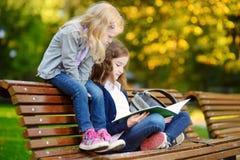 2 прелестных маленьких школьницы изучая в городе паркуют Стоковые Фотографии RF