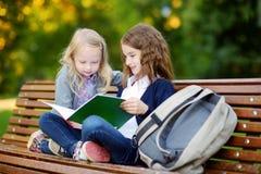 2 прелестных маленьких школьницы изучая в городе паркуют Стоковая Фотография RF