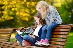 2 прелестных маленьких школьницы изучая в городе паркуют Стоковое Изображение