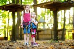 2 прелестных маленькой девочки наслаждаясь их временем в взбираясь приключении паркуют на теплый и солнечный летний день Стоковые Фото