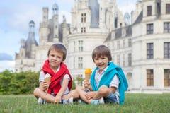 2 прелестных мальчика в вскользь одежде, есть мороженое сидя o Стоковая Фотография RF
