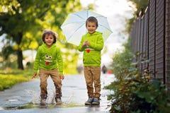 2 прелестных мальчика, играя в парке на дождливый день, играют Стоковая Фотография