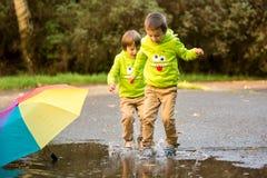 2 прелестных мальчика, играя в парке на дождливый день, играют Стоковая Фотография RF