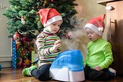 2 прелестных мальчика играя с работая увлажнителем, ждать x-mas Стоковая Фотография