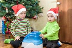 2 прелестных мальчика играя с работая увлажнителем, ждать x-mas Стоковое Изображение