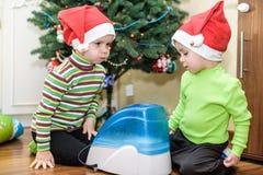 2 прелестных мальчика играя с работая увлажнителем, ждать x-mas Стоковое фото RF