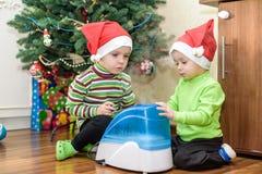 2 прелестных мальчика играя с работая увлажнителем, ждать x-mas Стоковые Фото