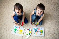 2 прелестных мальчика, подготавливая подарок дня отцов для папы, крася Стоковое Изображение