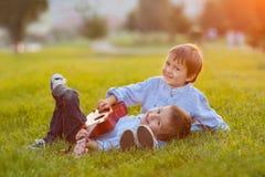 2 прелестных мальчика, сидящ на траве, играя гитару Стоковые Изображения RF