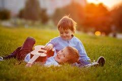 2 прелестных мальчика, сидящ на траве, играя гитару Стоковое фото RF