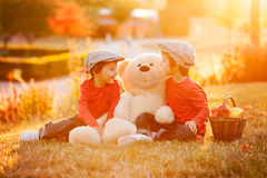 2 прелестных мальчика с его другом плюшевого медвежонка в парке Стоковые Фотографии RF
