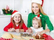 2 прелестных сестры с ее печеньями рождества выпечки матери Стоковое Фото