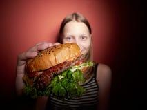 Предназначенная для подростков девушка есть бургер стоковое фото